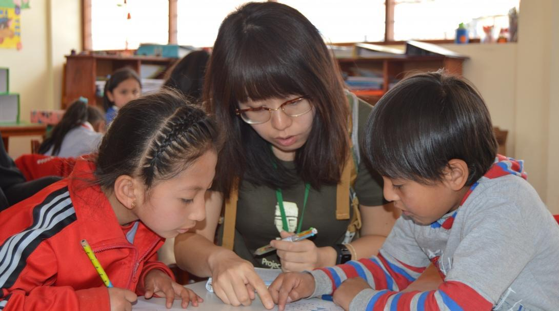 Teenage volunteers doing work with children in Peru, help in the classroom with activities.